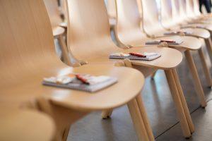 Muisitiinpanovälineita luentosalin tuoleilla