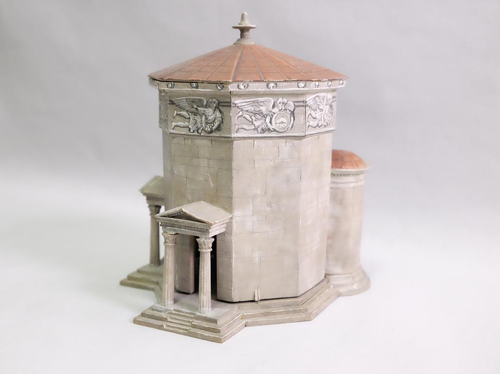 Tuulten tornin pienoismalli on vaaleanharmaa, punakattoinen kahdeksankulmainen torni.