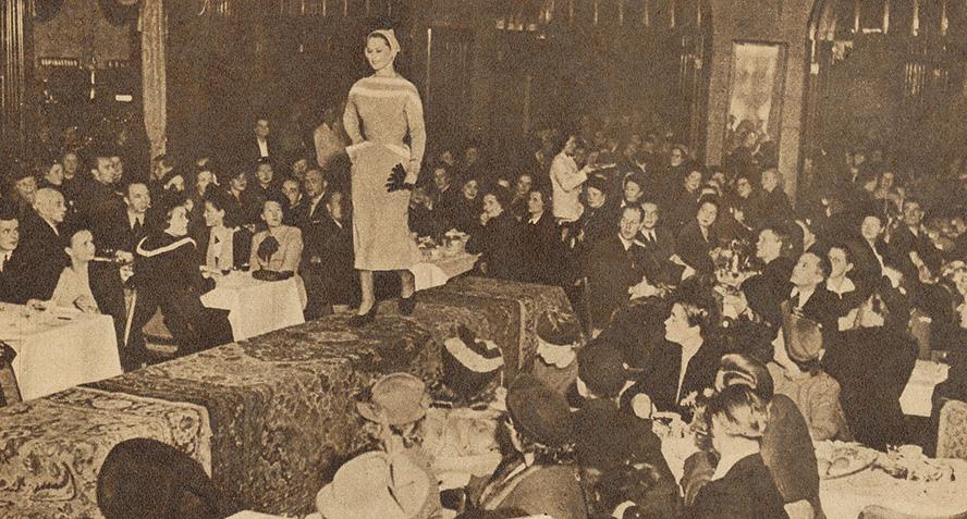 Mustavalkoinen kuva muotinäytöksestä, istuva yleisö, jonka keskellä catwolilla kävelevä malli.