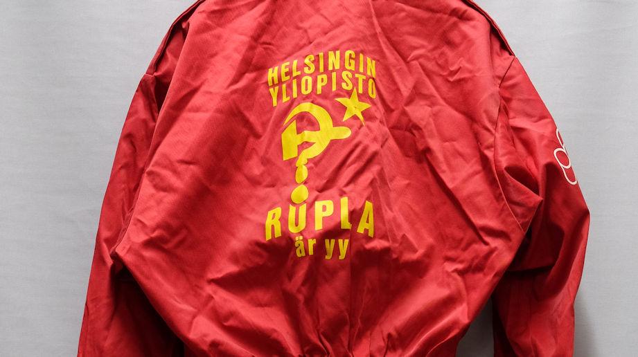Neuvostoliittoon viittaavat symbolit vasara ja kysymysmerkiksi tyylitelty sirppi sekä tekstiä painettuina punaisessa, hieman ryppyisessä vaatteessa.