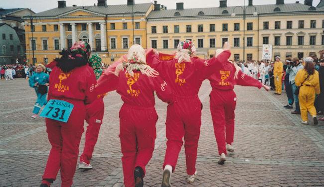 Neljä punaiseen haalariin pukeutunutta nuorta naista juoksevat rinnakkain poispäin huivit päässä Senaatintorilla Tuomiokirkolta Aleksanterinkadun suuntaan. Yhdellä on takapuolen päälle kiinnitetty lappu, jossa numero 731. Oikealla keltaisiin, vihreisiin ja valkoisiin haalareihin pukeutunutta yleisöä.