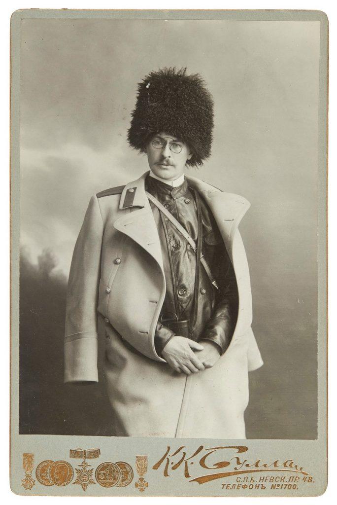 Mustavalkoinen valokuva nuorehkosta Backmanssonista, jolla päässään korkea turkishattu, harteilla vaalea päällystakki.