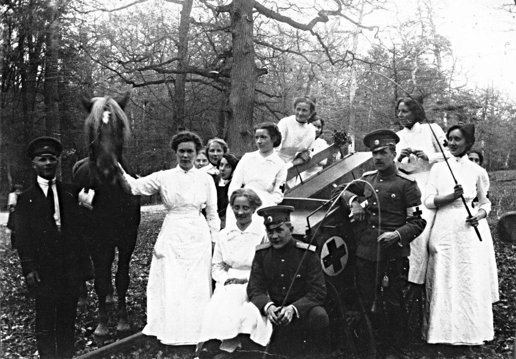 Sairaanhoitajia valkoisissa puvuissa ja lääkäreitä univormuissa ulkona, mahdollisesti retkellä. Seurue on kokoontunut ryhmäkuvaan hevosen ja Punaisen Ristin tunnuksella varustettujen kärryjen luo. Taustalla on puita.