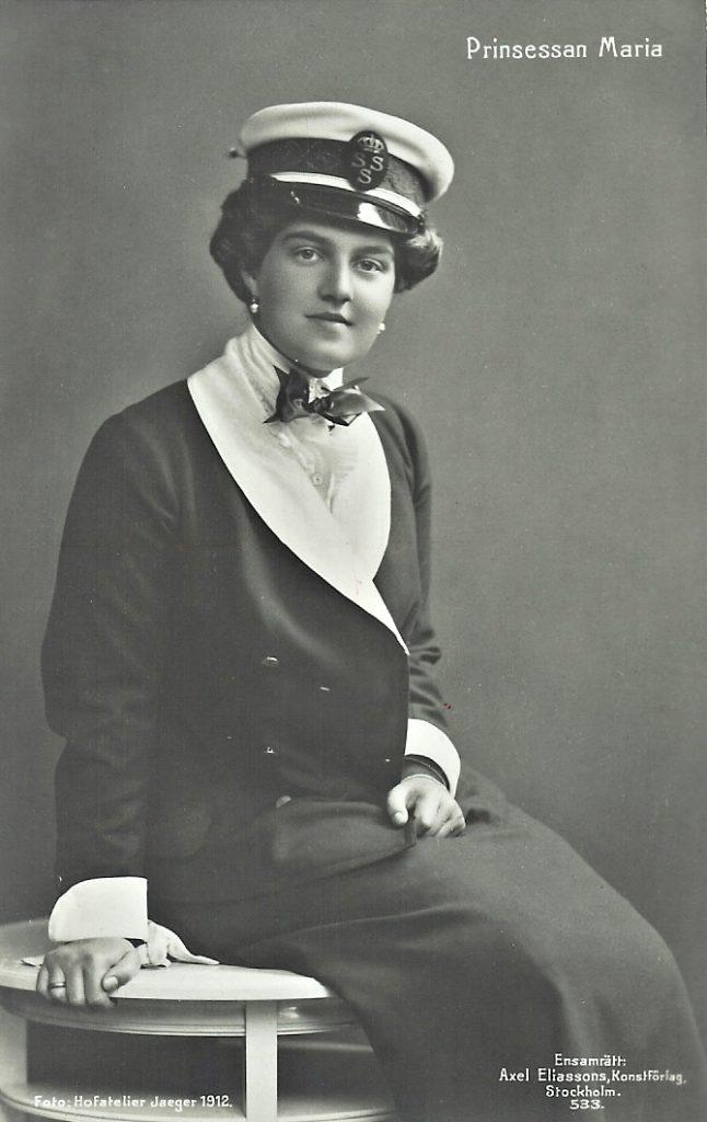 Tummaan takkiin ja hameeseen sekä valkoiseen paitaan pukeutunut nainen istuu penkillä ja katsoo suoraan kameraan. Päässään naisella on lipallinen lakki.