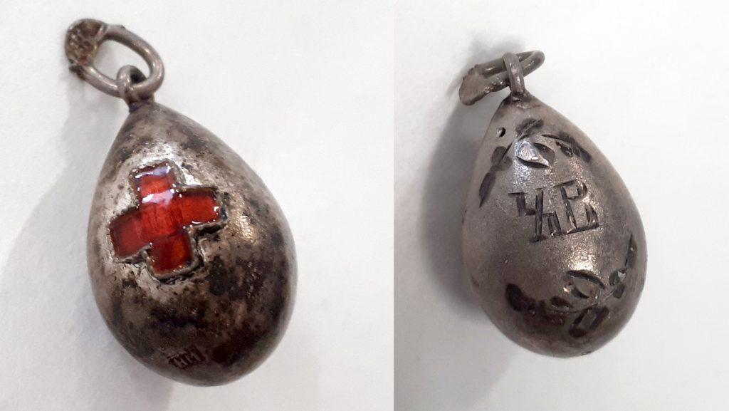 Pieni munanmuotoinen riipus, jota koristavat Punaisen Ristin tunnus ja kyrilliset XB-kirjaimet.