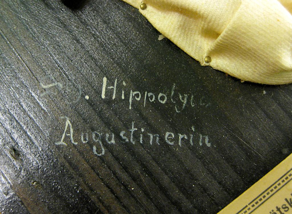 Lähikuva mustaksi maalattuun puuhun valkoisella kirjoitetusta signeerauksesta. Oikeassa yläkulmassa näkyy hiukan valkoista kangasta ja neula, jolla kangas on kiinnitetty taustaan. Oikeassa alanurkassa näkyy hiukan vahakuvan etikettiä.