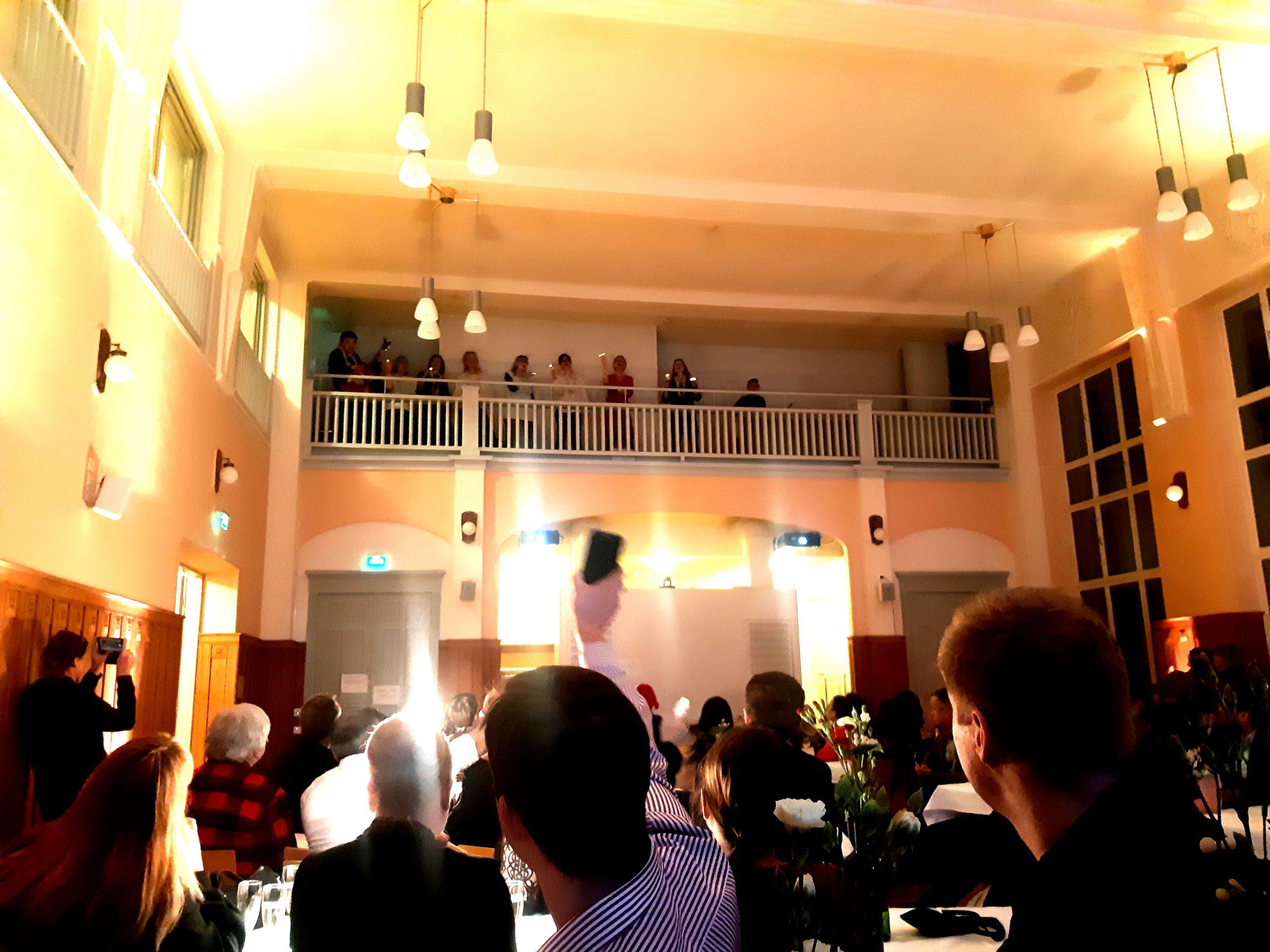 Lauluyhtye esiintyy juhlasalin parvella ja ihmiset heiluttavat käsiään