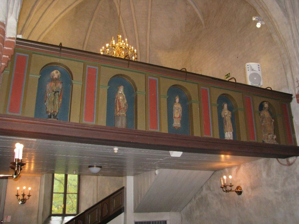 Hollolan kirkon (rak. n. 1500) urkuparveen on sijoitettu kymmenen eri kokonaisuuksista peräisin olevaa, eri ikäistä ja eri puulajeista valmistettua moniväristä veistosta. Kuvassa viisi pohjoispuolen veistosta. Kuva: Elina Räsänen.