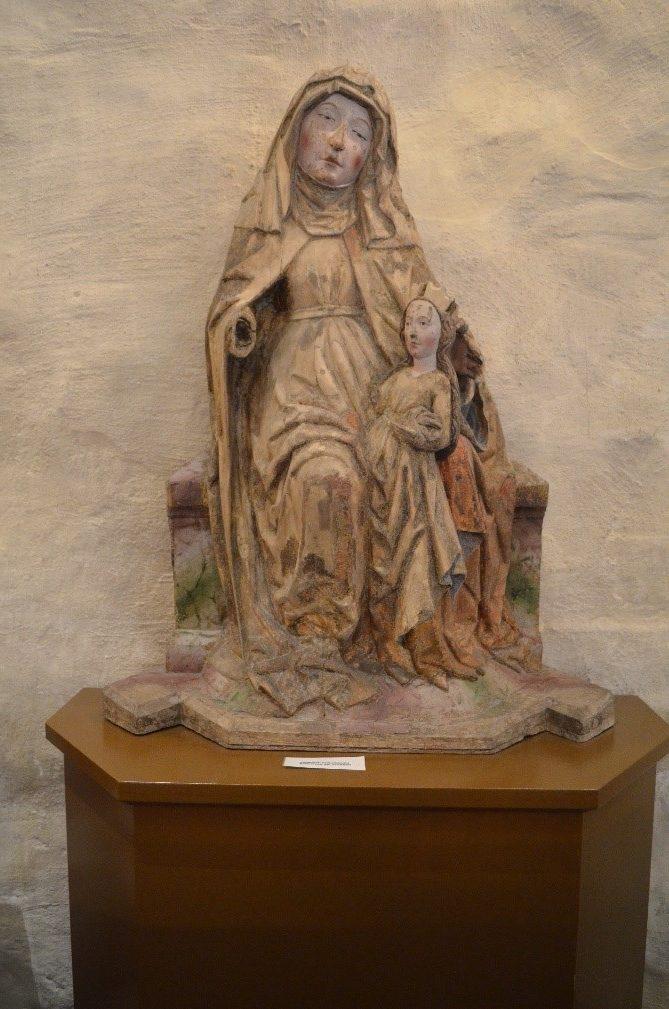 Pyhä Anna itse kolmantena, monivärinen keskiaikainen puuveistos, vaalea lehtipuu, n. 1490. Hollolan kirkko, sijoitettu eteläseinän eteen. Jeesus-lapsi puuttuu, samoin Pyhän Annan oikea käsi ja Neitsyt Marian kruunun sakarat. Alkuperäistä väriä säilynyt eniten kasvoissa. Kuva: Katri Vuola.