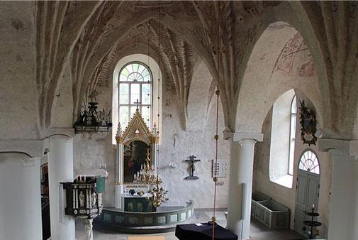 Siuntion keskiaikaisen kivikirkon kuori-ikkunan edessä on 1700-luvun alttaritaulu. Seinällä sen oikealla puolella on krusifiksi vuoden 1633 alttarilaitteesta. Kuva: Abc10, Wikimedia Commons, CC BY-SA 4.0, kuvaa rajattu.
