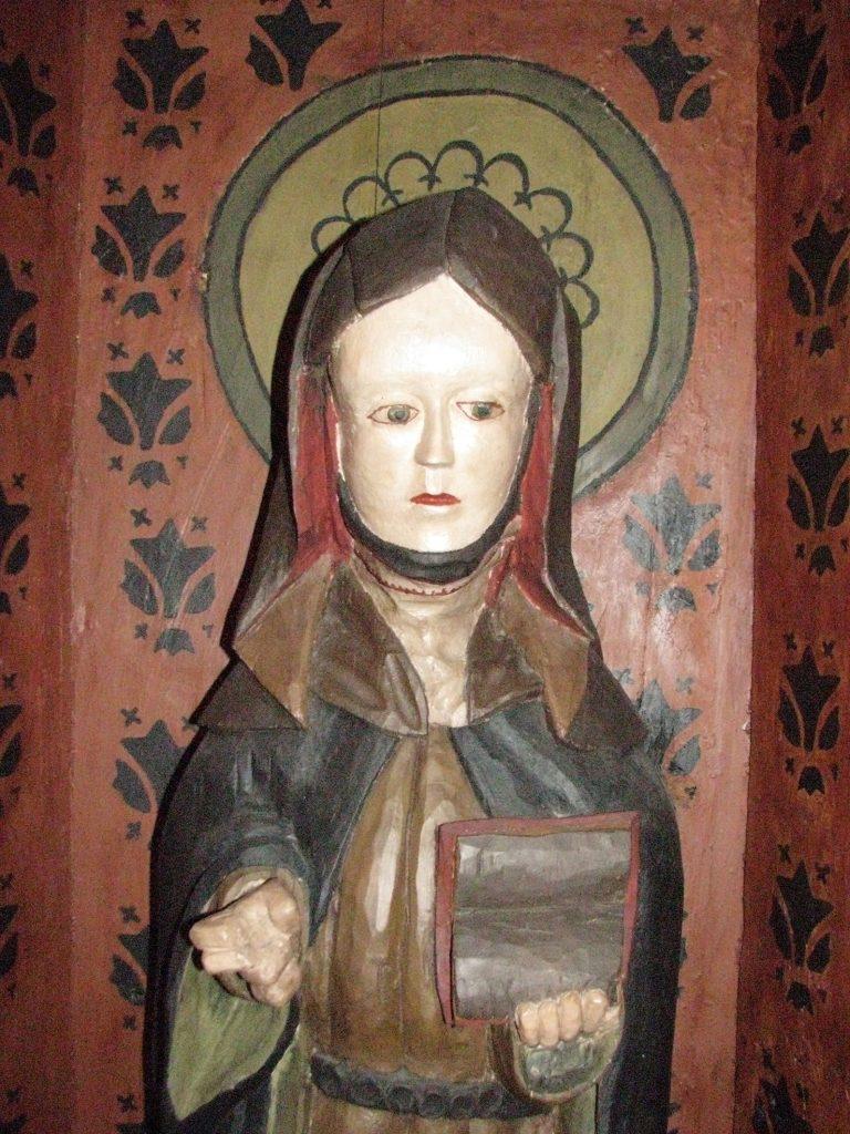 Maalattu puuveistos esittää huntupäistä naista, joka pitelee kädessään kirjaa. Naisen kasvot ovat vaaleat ja vaatteet ruskeansävyiset. Veistos on kaapissa, jonka seinät ovat punaiset ja koristellut mustilla kuvioilla. Veistoksen pään taakse on maalattu vihertävä sädekehä.