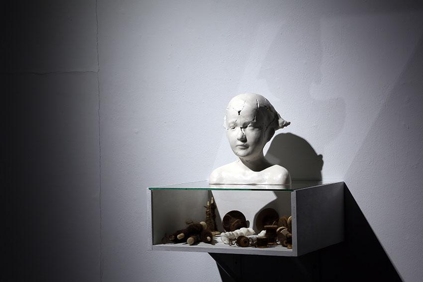 Harmaata seinää vasten on taideteos, jossa lasikattoisessa laatikossa on erilaisia esineitä. Laatikon päällä on valkoinen patsaan rintakuva, jonka kasvot ovat pirstoutuneet.