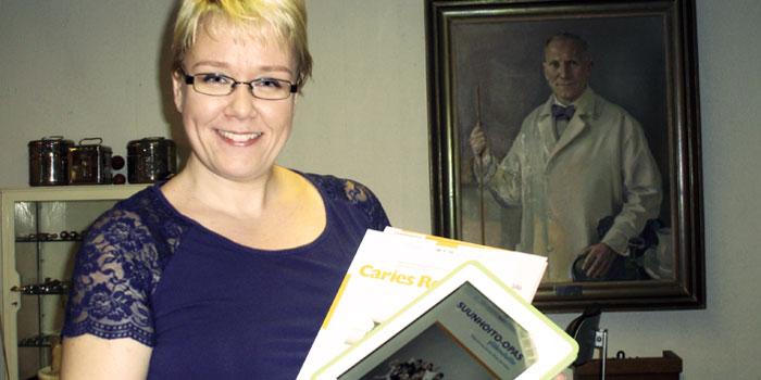 Kirjastosihteeri Anni Träff taustallaan professori Eero Sakari Tammisalo, odontologian tohtori. Proteesiopin   opettaja v. 1922- ja hammaslääketieteen laitoksen esimies 1925-194