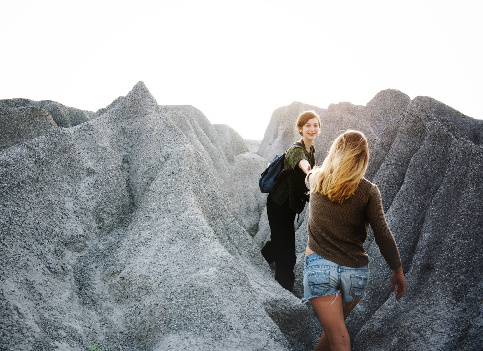 Polullaan pidemmälle ehtinyt nainen auttaa ystäväänsä kulkemaan kivikossa.