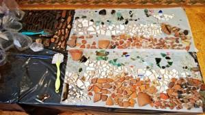 Puhdistetut löydöt käydään läpi ja moderni aineisto, kuten kukkaruukun palaset, poistetaan.