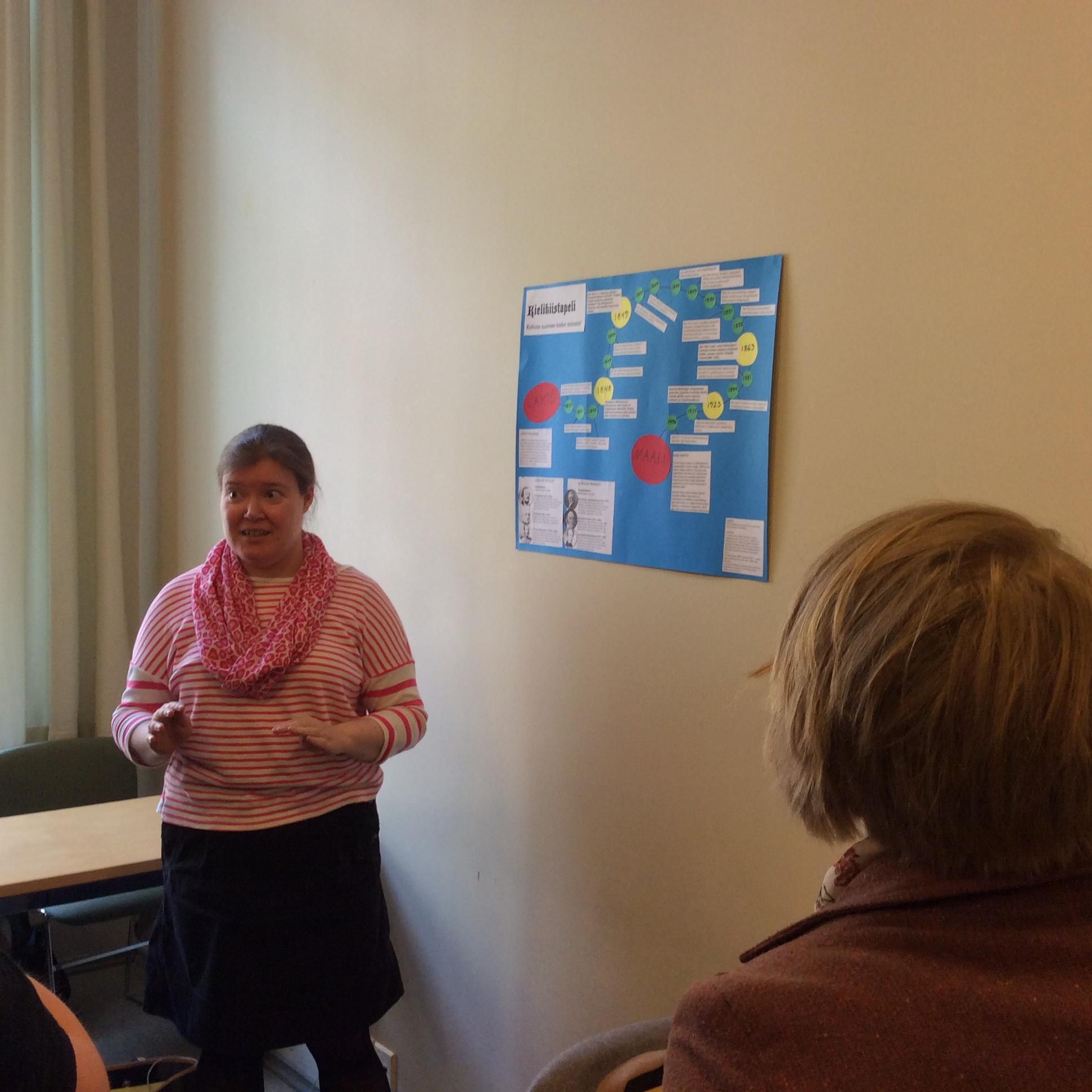 """2)Kristiina Kurki esittelee ryhmänsä posteria, jossa Suomen Lääkäriseurassa käyty kielikiista on puettu pelin muotoon.  Pelin """"pahikset"""" eivät luottaneet suomeen lääketieteen kielenä, kun taas """"hyviksistä"""" löytyi niitä, jotka rohkenivat kokeilla ja julkaista tutkimusta suomeksi."""