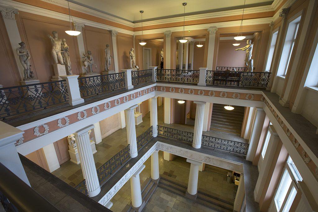 Näkymä päärakennuksen neljännestä kerroksesta sisäpihalle, vestibyylin alimpaan kerrokseen. Kipsiveistoksia näkyy eri kerroksissa.Näkymä päärakennuksen neljännestä kerroksesta sisäpihalle, vestibyylin alimpaan kerrokseen. Kipsiveistoksia näkyy eri kerroksissa.