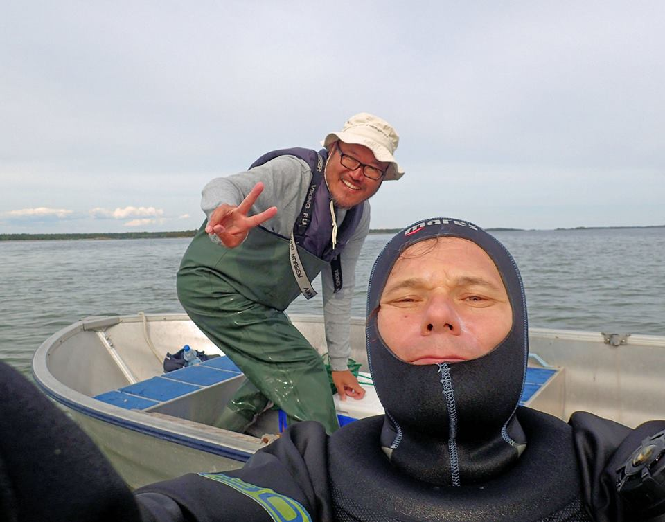Dr. Topi Lehtonen and Associate Professor Bob Wong on a small boat doing a selfie.