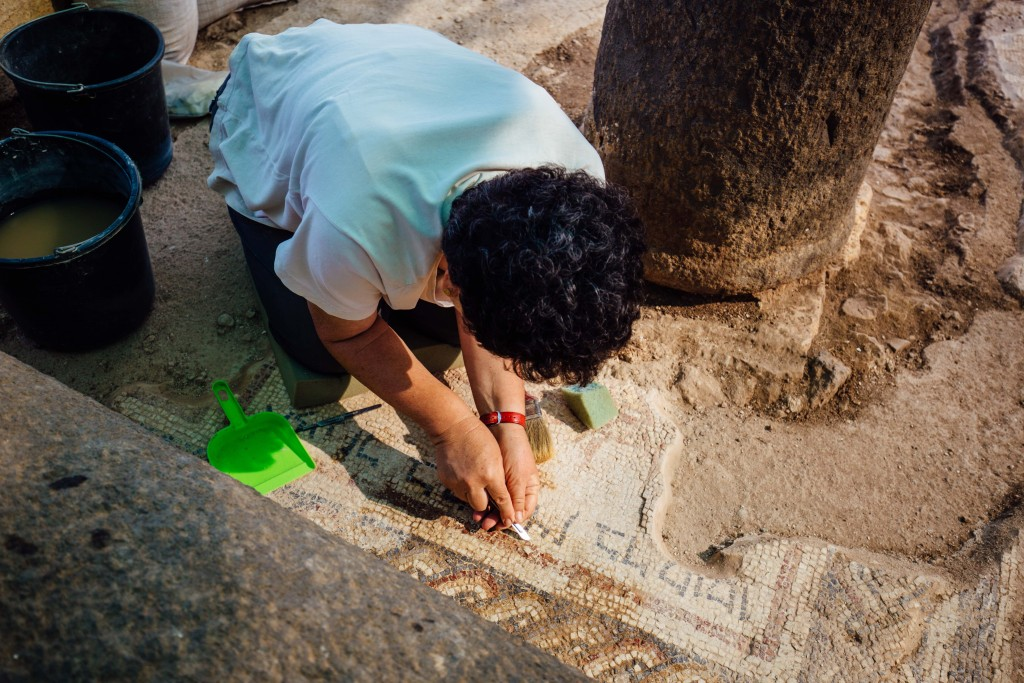 Restorer Orna Cohen busy cleaning the mosaic floor at Horvat Kur (photograph: Jaakko Haapanen; Copyright: Kinneret Regional Project)
