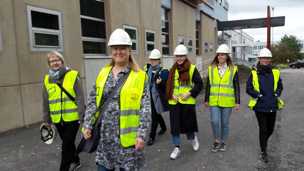 Kuusi naista huomioliiveissä ja valkoisissa työmaakypäröissä kävelee rakennuksen pihalla.