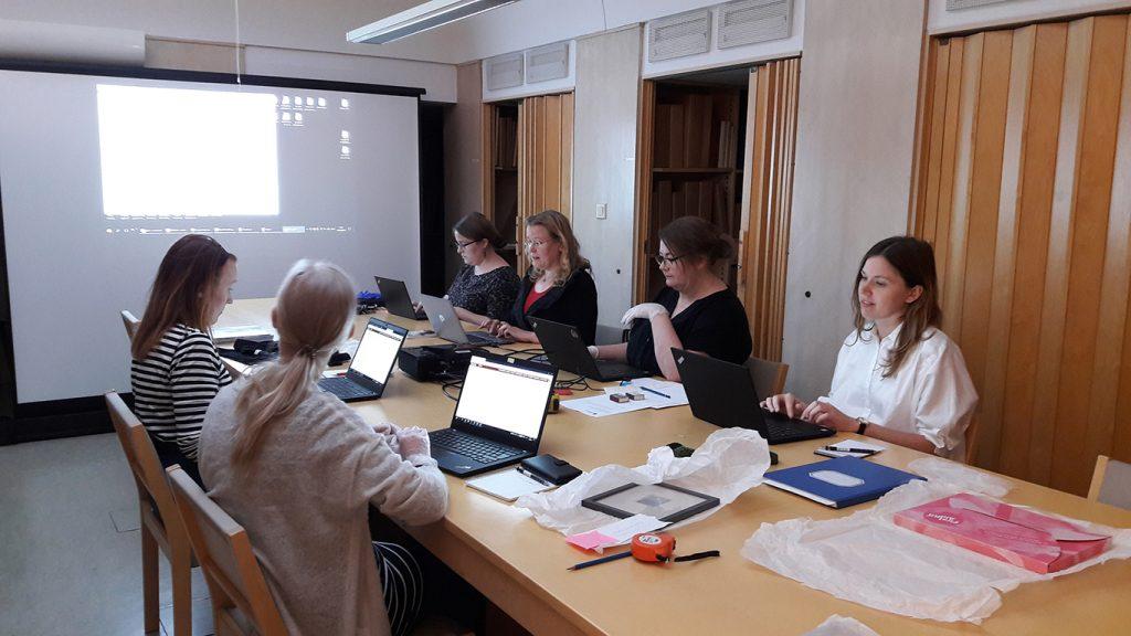 Pitkän pöydän molemmin puolin istuu tietokoneidensa äärellä naisia.