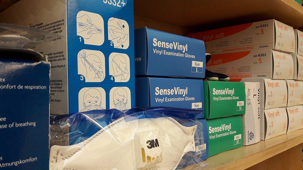Pahvisia suojavarustepakkauksia, joissa on hanskoja ja hengityssuojaimia.