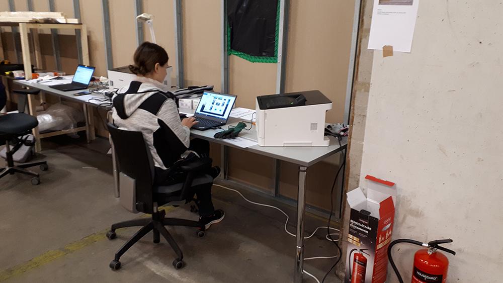 Museotyöntekijä työpöydän ja tietokoneen ääressä.