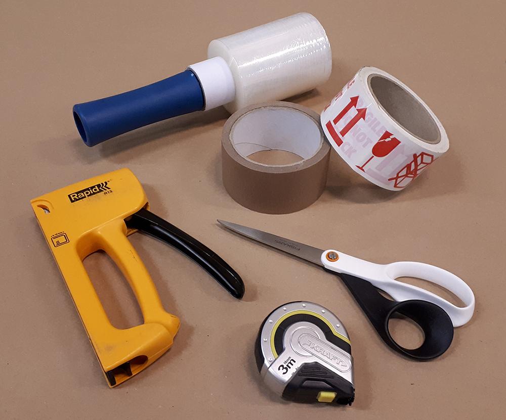 Kiristekalvorulla, paperiteippiä ja varoitusteippiä, sakset, mittanauha ja niittipistooli.