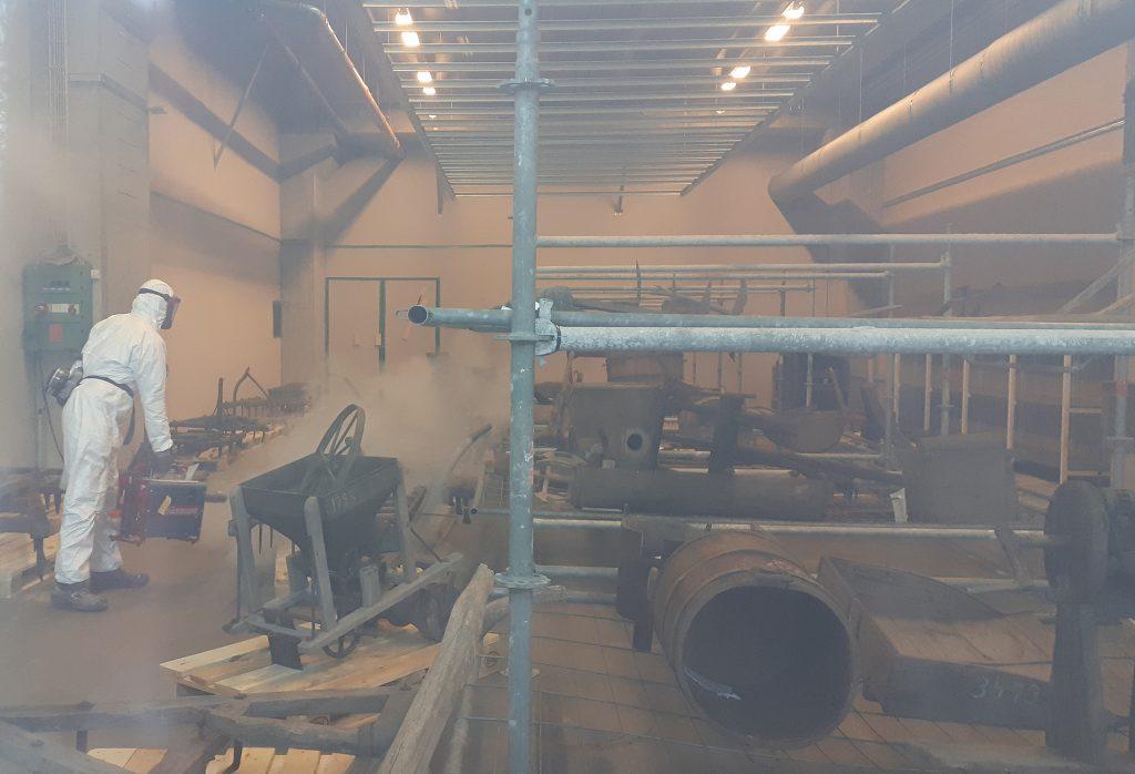 Danotecin työntekijä suihkuttaa vetyperoksidia hyllyillä olevien esineiden päälle.