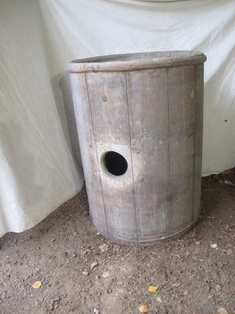 Puinen tynnyri, jonka kyljessä on pyöreä reikä.