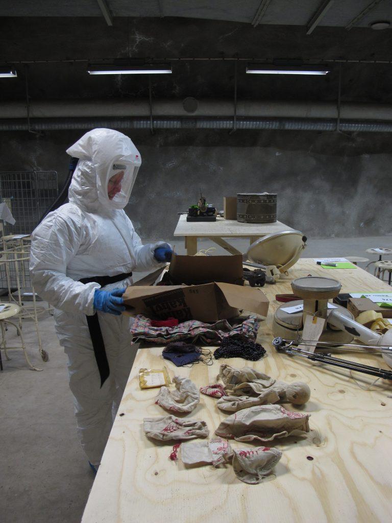 Museotyöntekijä käy läpi esineitä pöydän ääressä. Hänellä on päällään valkoinen suoja-asu ja kädessä siniset nitriilihanskat.
