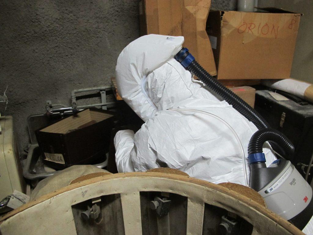 Valkoisessa suoja-asussa ja moottoroidun hengityssuojaimen kanssa työskentelevä museotyöntekijä ahtaassa tilassa.