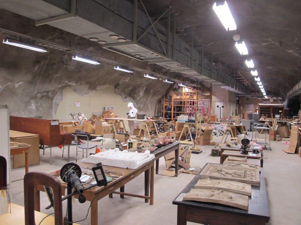 Kalliosuojan työskentelytila on täynnä pöytiä ja niille inventoitaviksi kannettuja esineitä.