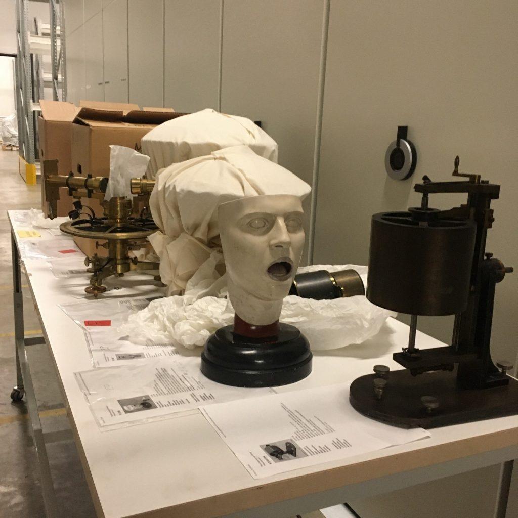 Esineitä pöydällä odottamassa nostamista hyllyyn. Etualalla on kipsinen ihmiskasvojen malli sekä metallista valmistettuja tutkimuslaitteita.