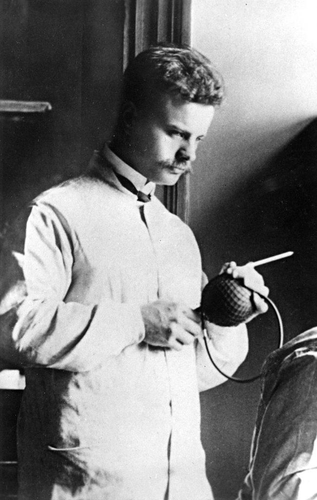 Mies lääkärintakissa pitelee käsissään instrumenttia. Kuva on mustavalkoinen.