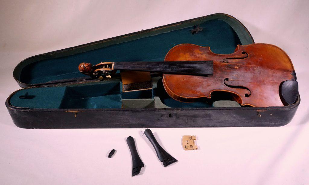Puinen, musta viulukotelo, joka on verhoiltu viheällä sametilla. Kotelossa lepää punaruskea viulu ja kotelon edessä puinen talla ja mustia kielenpitimiä.