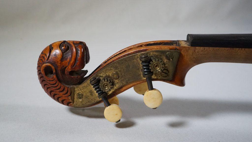 Viulun pää, joka on muotoiltu leijonan pääksi. Metalliset ja norsunluiset viritystapit.