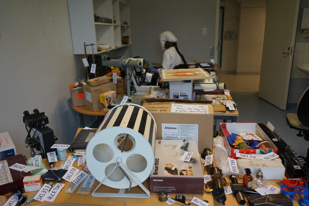 Kuvassa valkoiseen moottorihuppuun sonnustautunut museotyöntekijä työskentelee runsaans esinemäärän keskellä. Esineet levitelty pöydille.