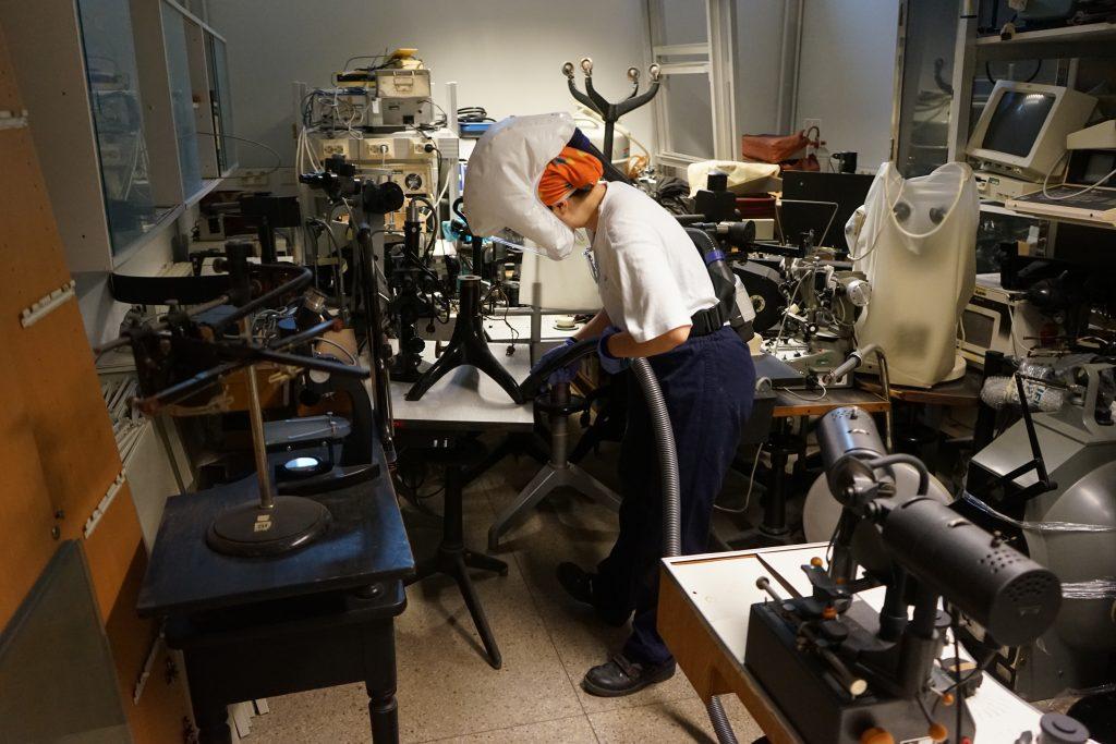 Museotyöntekijä imuroi esineitä kellarissa. Isot esineet ovat levällään ympäri huonetta työntekijän molemmilla puolilla.