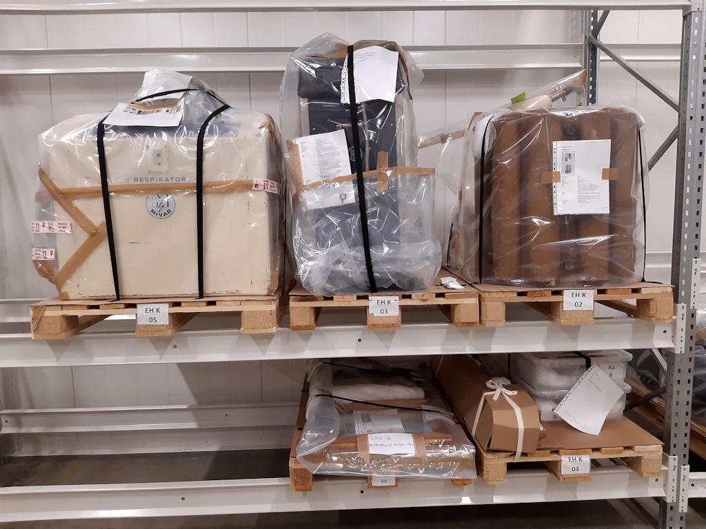 Suurikokoisia karanteenimuoviin pakattuja laitteita kokoelmakeskuksessa.