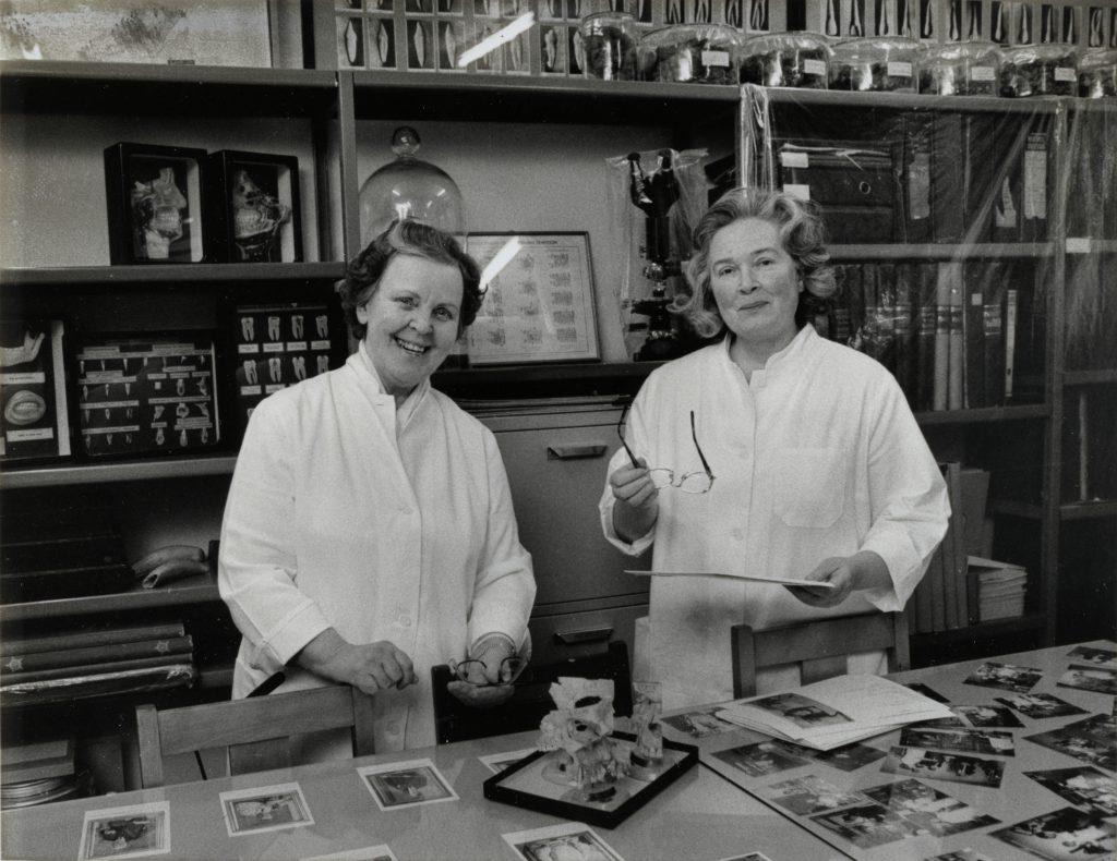 Kuvassa etualalla hammashoitajat Tamminen ja Hakkarainen valkoisissa työtakeissaan. Heidän takanaan hyllyssä on hammaslääketieteen museoesineistöä.
