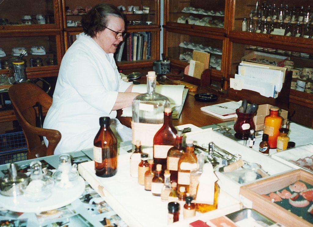Hammashoitaja istuu museovarastossa pöydän ääressä.