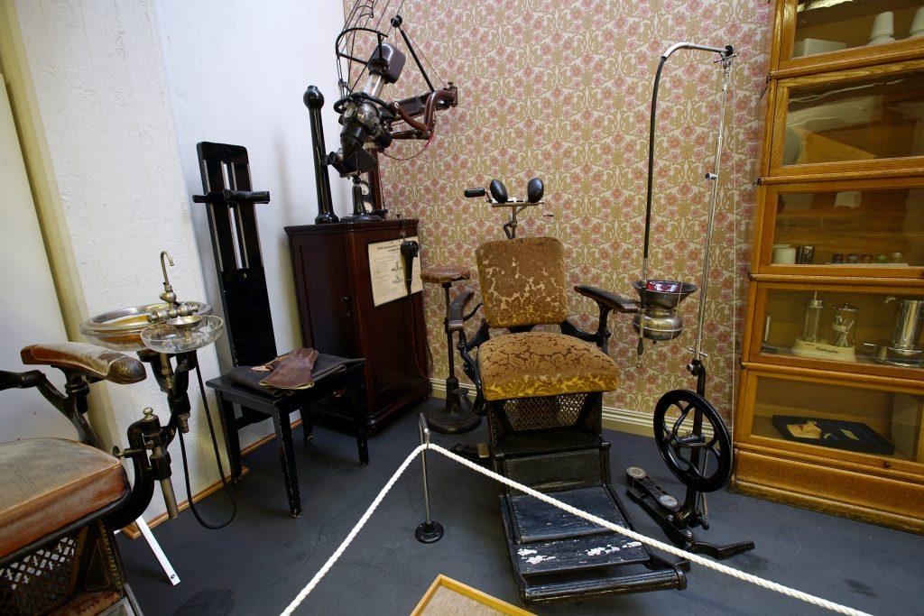 Kuvassa on plyysikankaalla päällystetty potilastuoli, vanha röntgenkone, jalkapora ja vitriinikaappi.
