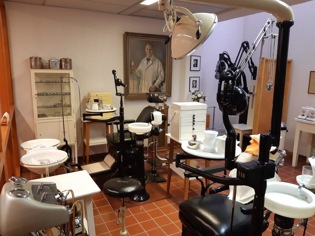 Kuvassa on eri-ikäisiä hammaslääkärien työskentely-yksiköitä, muotokuva, vitriinikaappi ja käsienpesualtaita.