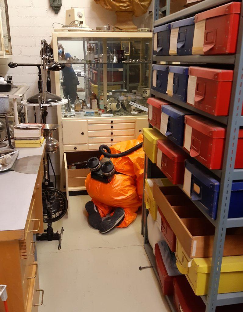 Suojahaalariin pukeutunut työntekijä on polvillaan hyllyjen välissä tutkimassa esineitä.