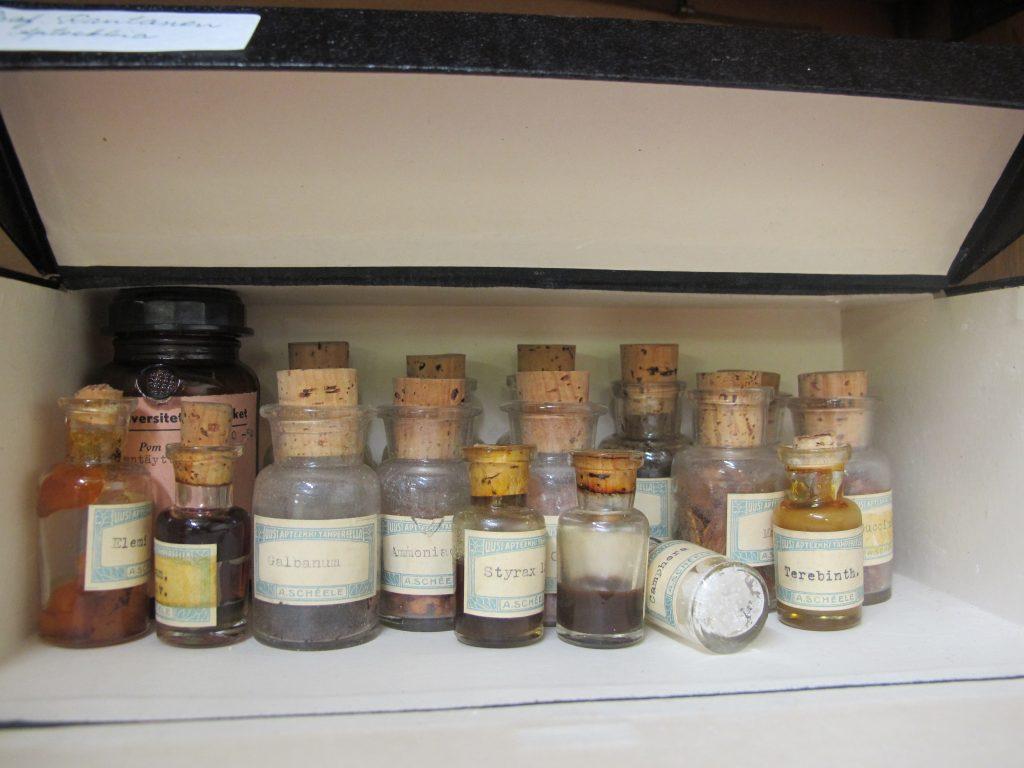 Lasisia pulloja, joissa erilaisia luonnonhartseja sisällä.