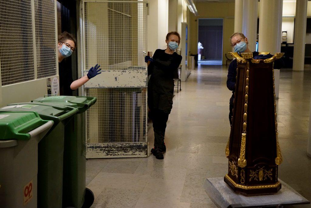 Kolme Yliopistomuseon työntekijää kuljettaa jalustaa ulos hissistä.