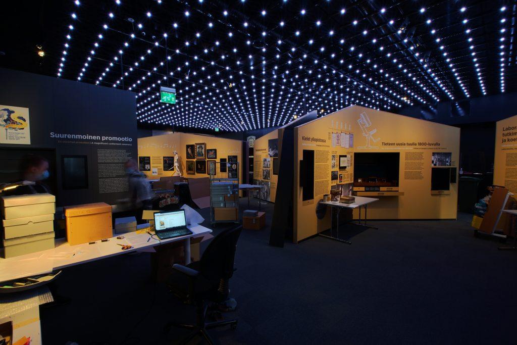 Ledilamppujen alla näyttelyrakenteita, esineitä sekä pakkausmateriaaleja.