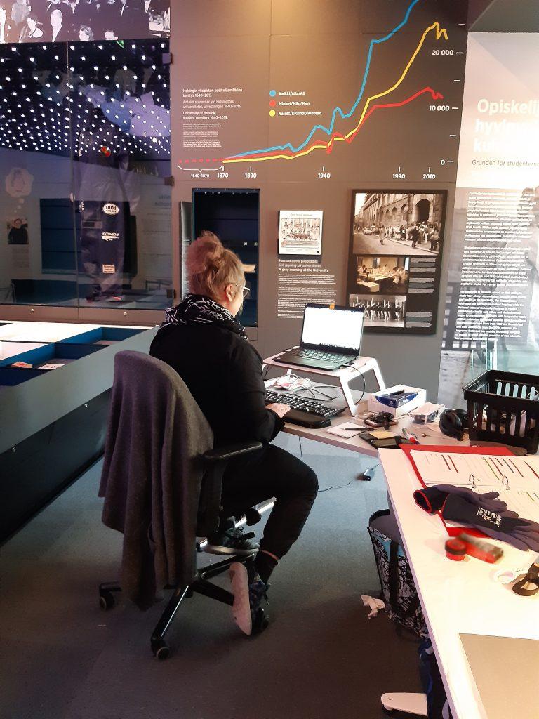 Nainen istuu tietokoneen ääressä selin kameraan. Vieressä punainen kansio, jossa paperisia esinelistoja.