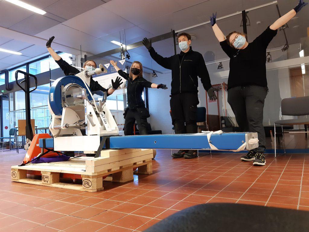 Neljä Yliopistomuseon työntekijää seisoo tulettamassa kädet ilmaan nostettuina lavalle kiinnitetyn röntgenkoneen takana